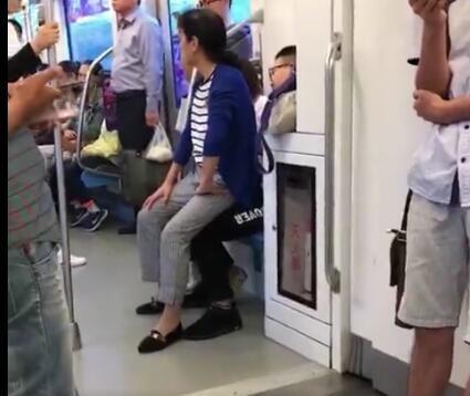 地铁上一小伙不肯让座 大妈直接坐到了他腿上