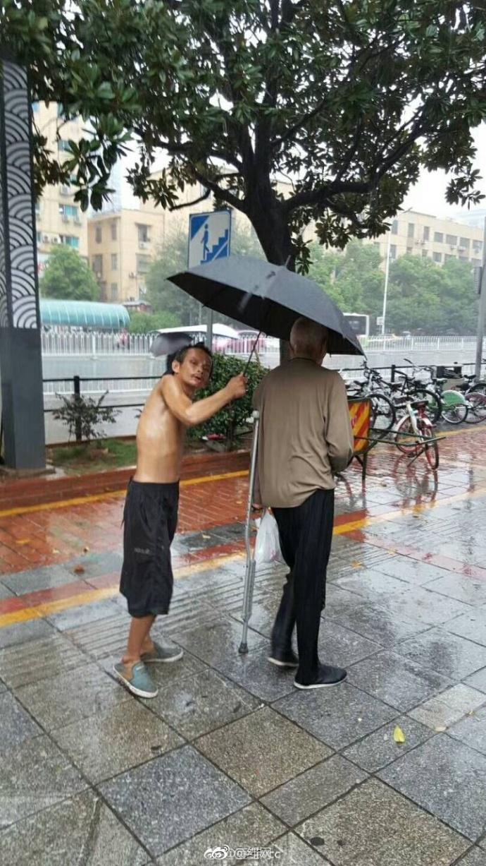 暴雨中 流浪乞丐为腿脚不便的老人撑伞(图)