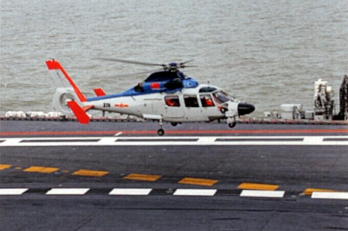 直-9直升机着舰  据央视报道,近日,国内某杂志刊登了一组辽宁舰航母训练照片,照片中不仅有歼-15舰载机挂弹训练的场景,还能看到一款改进型直-9直升机。军事专家杜文龙在接受央视《今日亚洲》采访时表示,直升机在航母上出现,说明航母作战体系正在逐步发展和完善。未来各种舰载机和直升机平台能否上航母,可能要由辽宁舰说了算。 据报道,这架直升机的涂装很有特点,机身上蓝下白,尾部旋翼、尾浆前方和整个尾梁都涂装了橙色。有评论认为,这架改进型直-9很可能是用于搜救的直升机,它的上舰意味着辽宁舰