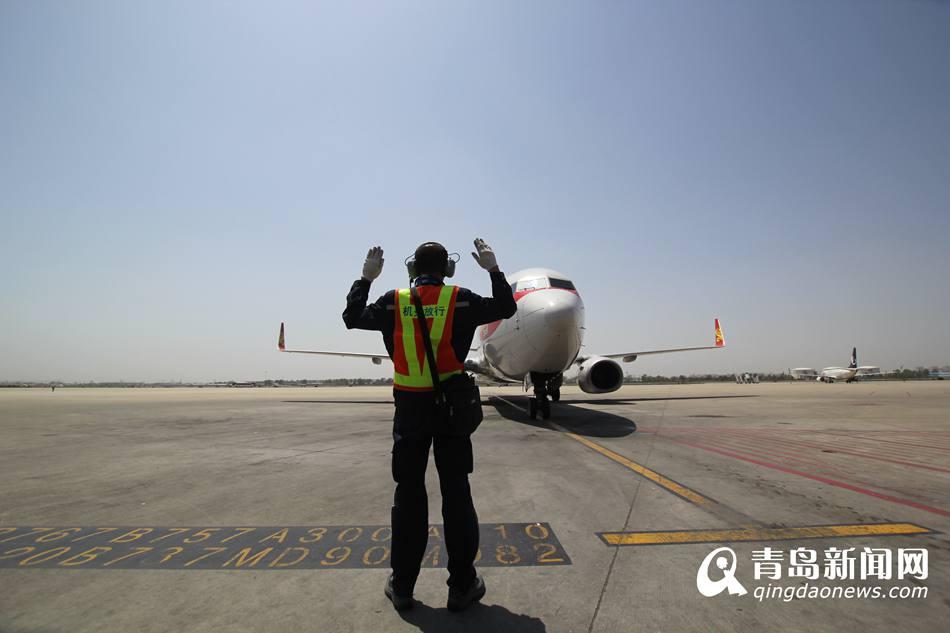 宋刚正在指挥一架飞机停泊指定地点.