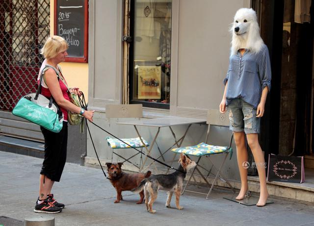 女人人体艺术狗_5月3日,法国尼斯,一名妇女和她的狗停在一个戴着狗头面具的人体模特前