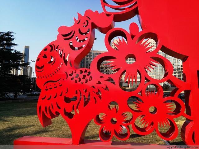 农历鸡年即将到来,近日,在青岛五四广场上矗立起巨幅红色雕塑,雕塑中以一个个不同字体的家字组合成巨大的一个福字,两边是剪纸手法的雄鸡唱晓和欢度2017春节的金色大字,寓意家和福乐多、鸡年再昂首。在香港路、东海路两侧路灯杆上和部分小区门口、商家门前等也悬挂起了红红的灯笼,吸引市民观赏拍照。