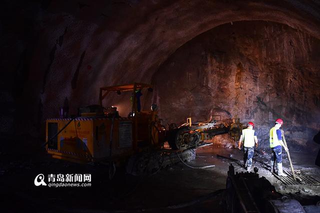 隧道中的三臂凿岩台车(受环境影响,画面中只有单臂在操作) 据了解,这台打孔机器名叫三臂凿岩台车,可以在坚硬程度较高的岩石上进行打孔作业,一次操作可以同时打三个直径9厘米的爆破孔,工作效率远超人工。据悉,地铁1号线是青岛地铁工程建设中唯一使用三臂凿岩台车打孔的线路。因凿岩台车可在坚硬程度较高的岩石上打孔,所以被用于1号线过海段的施工。  地铁1号线副总经理赵光泉告诉记者:1号线过海段全面推行机械化施工,海域段采用超前地质钻探保安全。过海段施工作业配备三臂凿岩台车、湿喷机、超前地质钻机等设备代